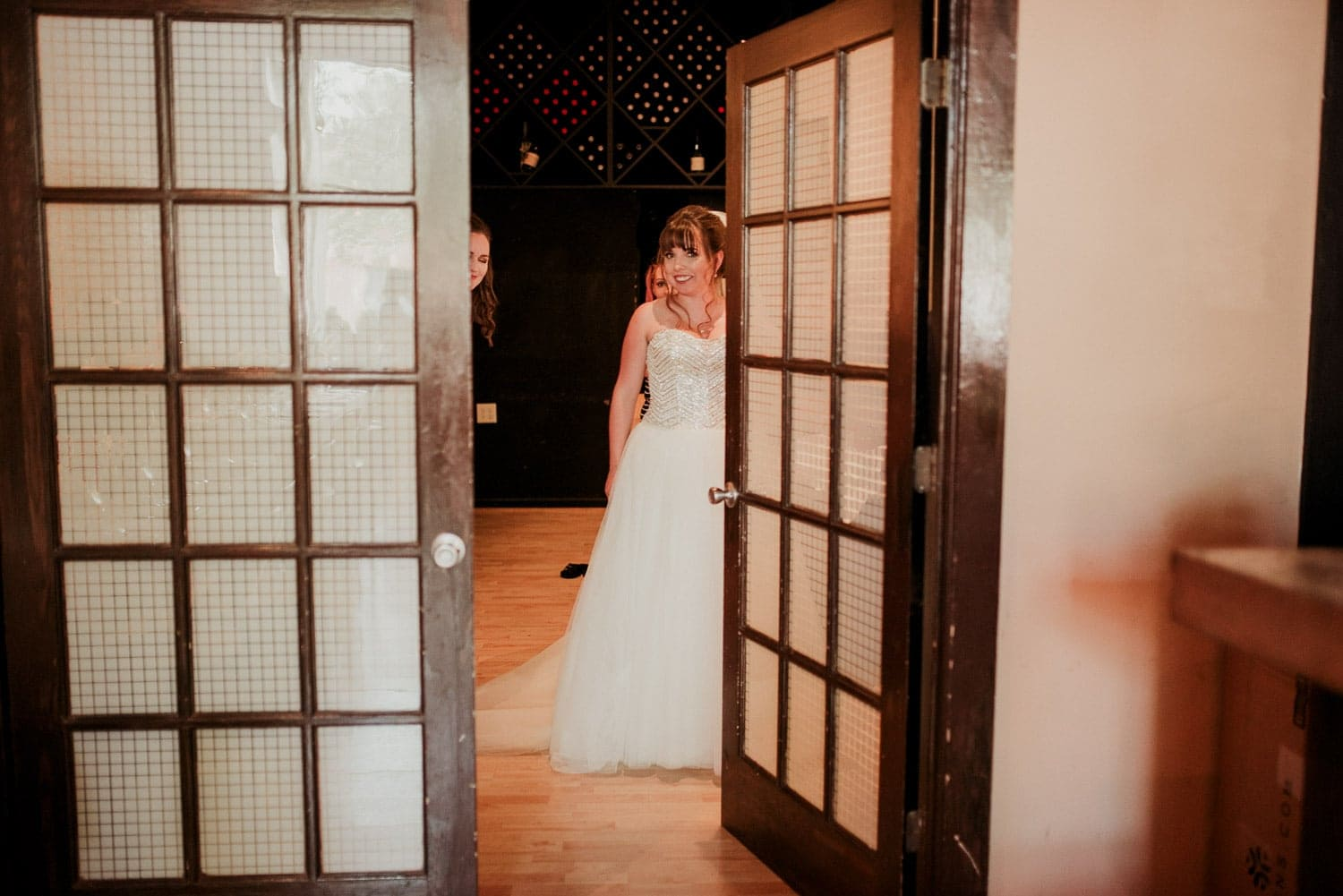 The bride is peeking out from behind an open door as she prepares to show everyone her wedding gown.