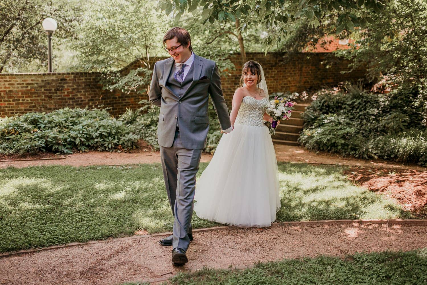 The bride and groom are holding hands. The groom is facing away from the bride. They are in a green garden at the University of Virginia.