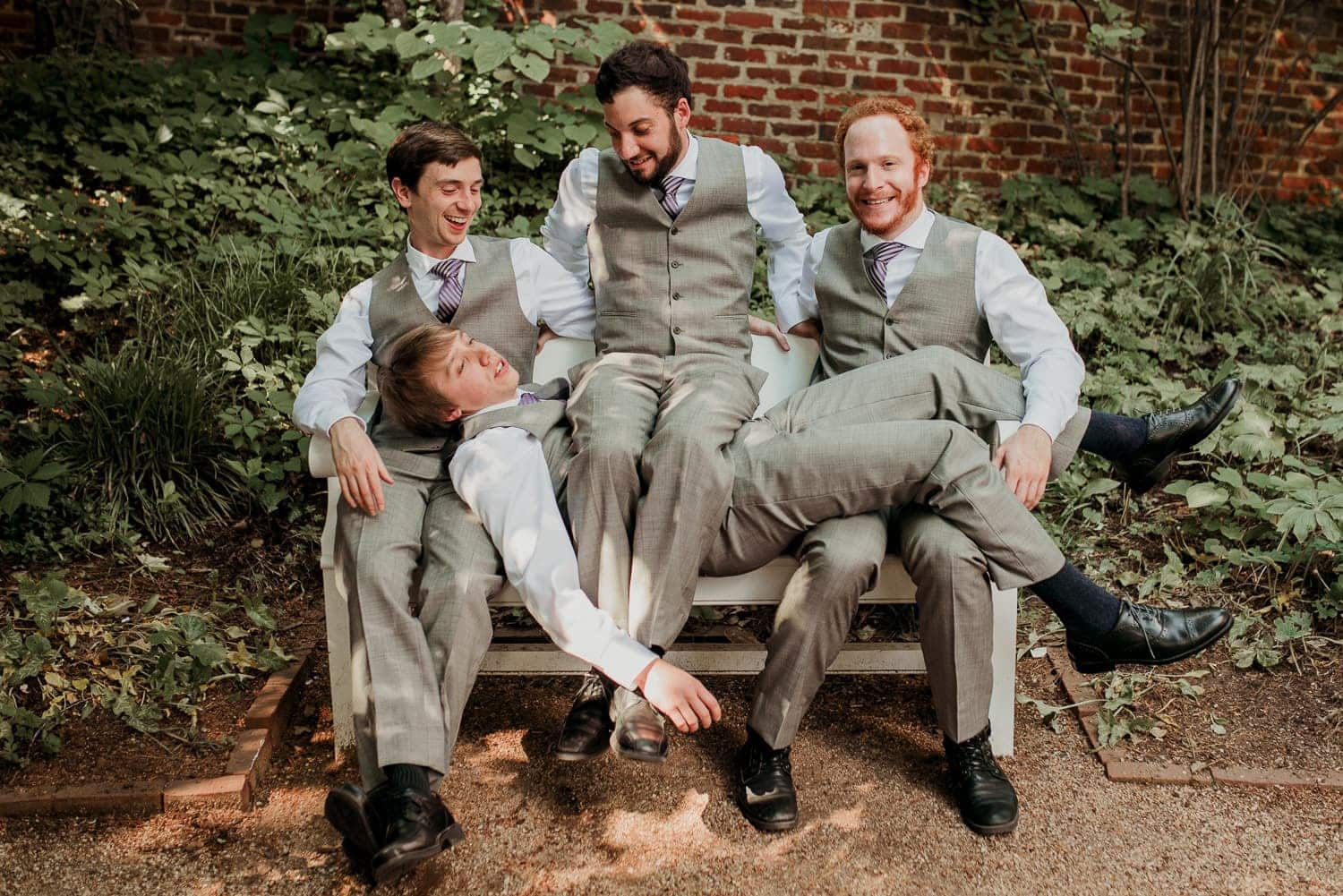 The groomsmen are being silly. One is sitting on top of another.