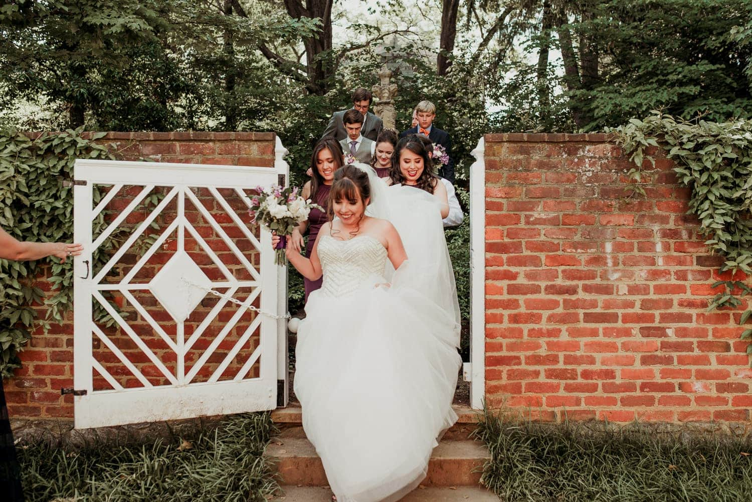 The bride is walking down steps with a smile on her face. The whole wedding party is behind her.