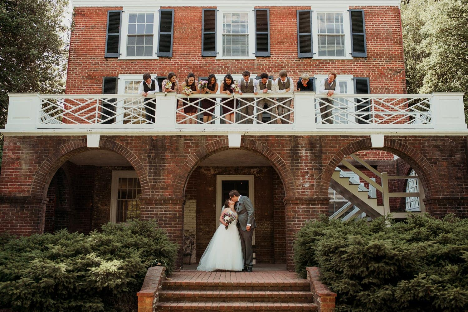 The bride and groom are kissing below a balcony where their wedding party is standing and looking at them.