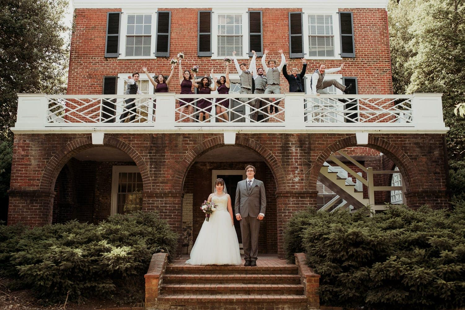 The bride and groom are holding hands and facing the camera. The wedding party is above them on a balcony. They are leaping in the air.