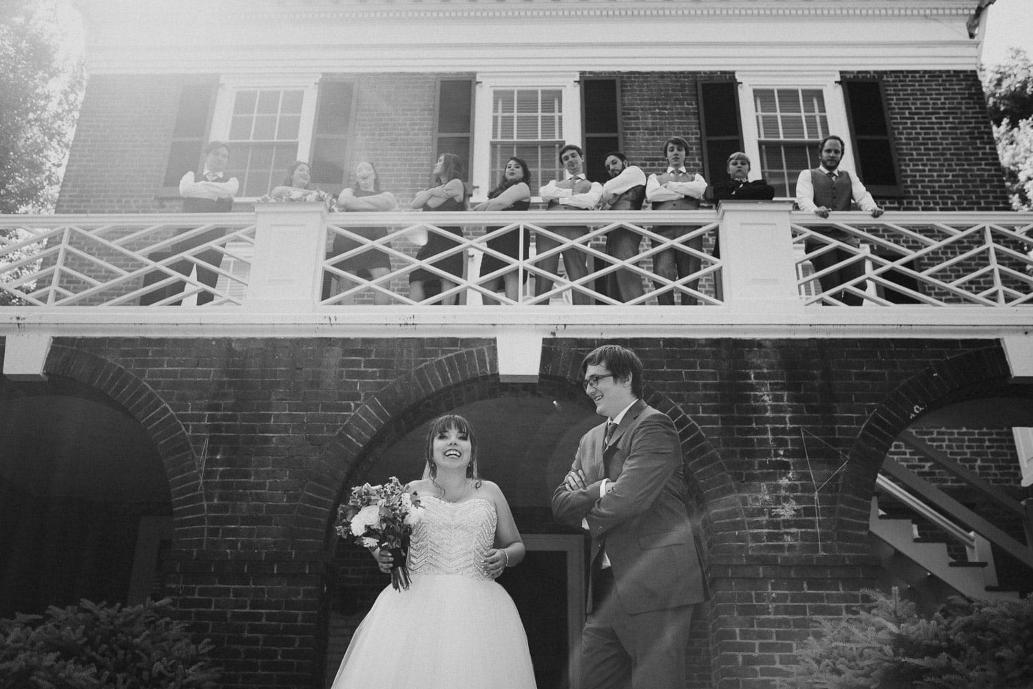 The bride and groom are laughing. They are standing in front of a brick building at the University of Virginia.
