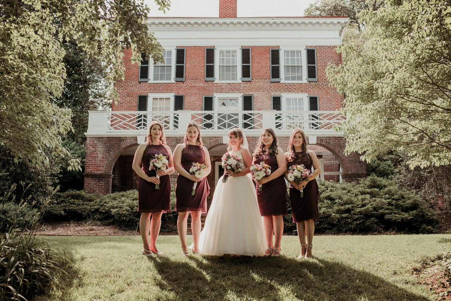 Bridal party in front of a two story brick building at Virginia state university