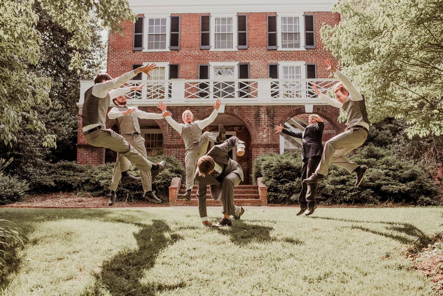 The groom appears to be punching the ground. His groomsmen are jumping in the air.