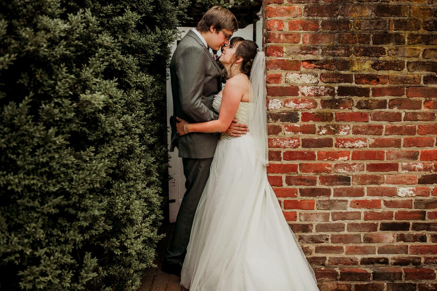 The bride and groom are holding each other close as they stand in a doorway.