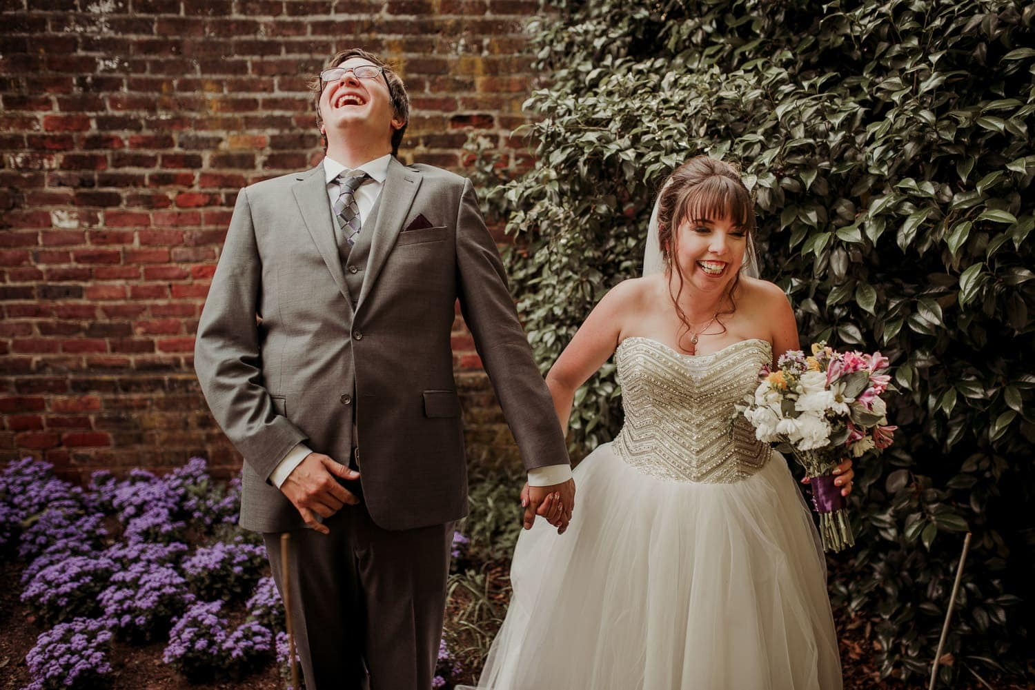 The bride and groom are holding hands and laughing.