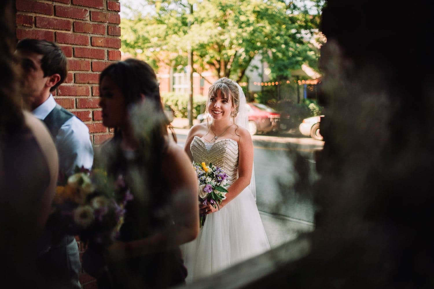 The bride is standing outside smiling as she waits to be escorted into her wedding.
