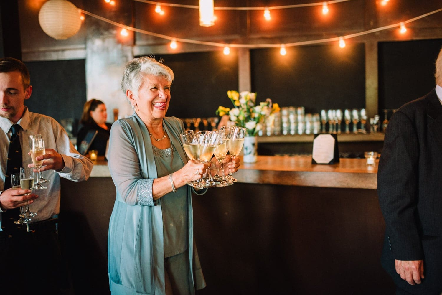 A wedding guest is smiling and carrying champaign glasses to the bride and groom.