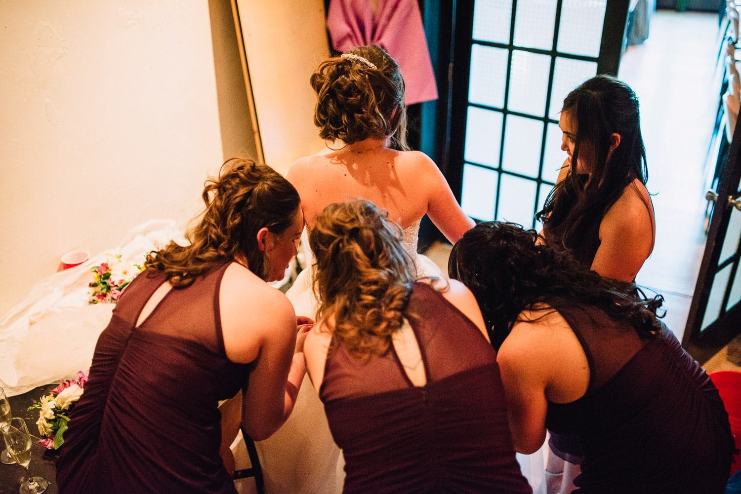 The bridesmaids are assisting the bride with her dress.