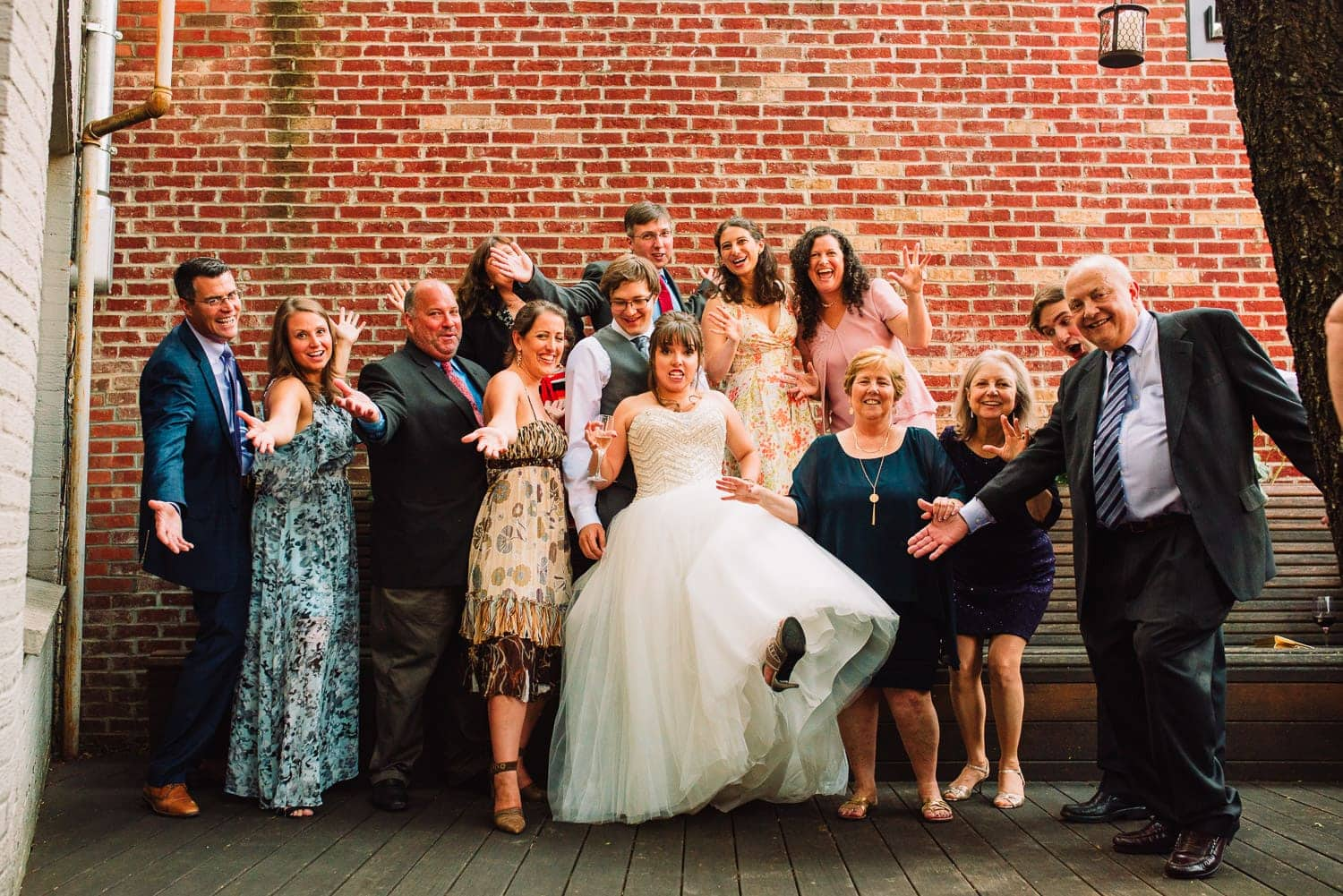 Bride, groom, and wedding guests acting silly for a picture