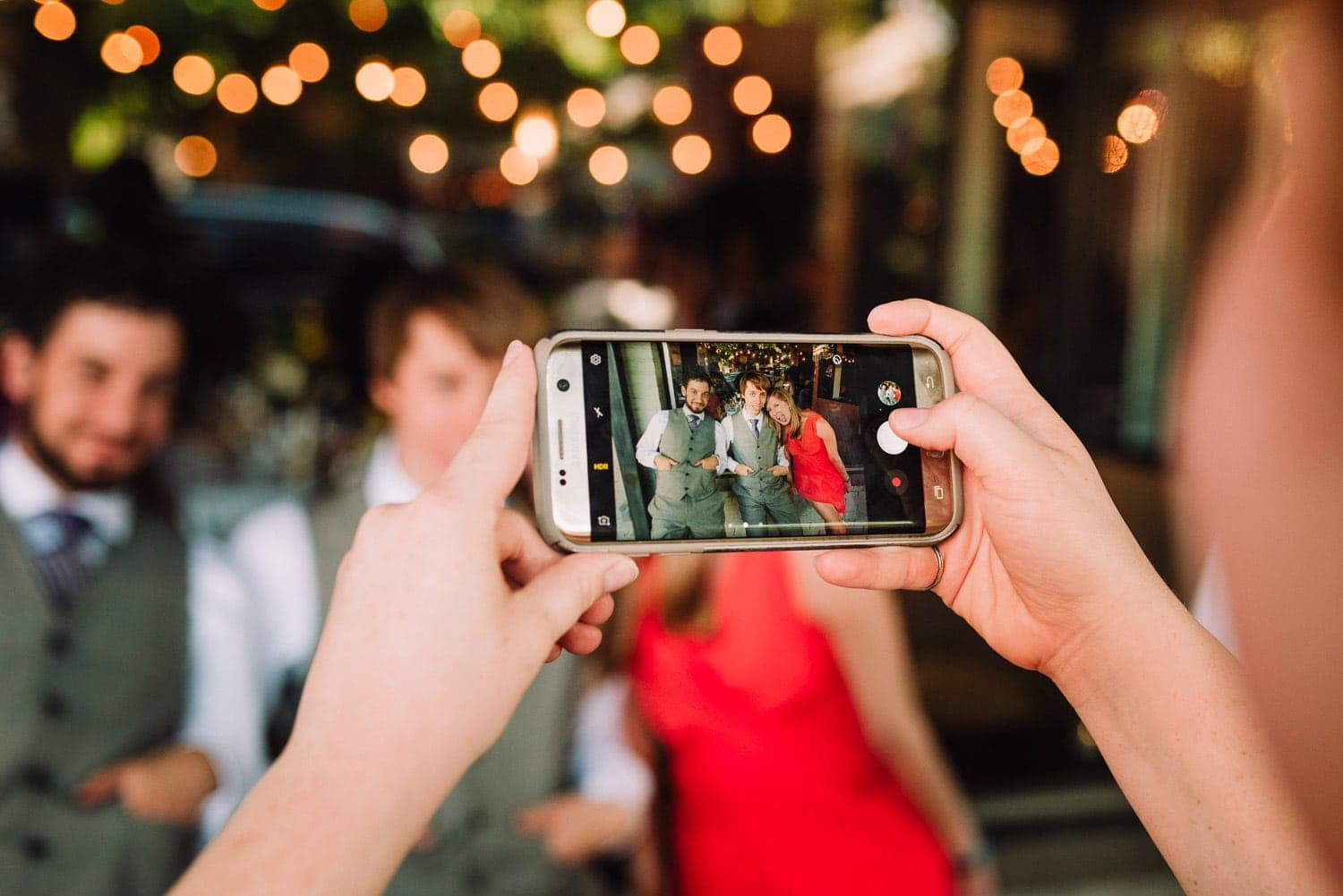 Close view of a smartphone with the image of two groomsmen and a friend on it.