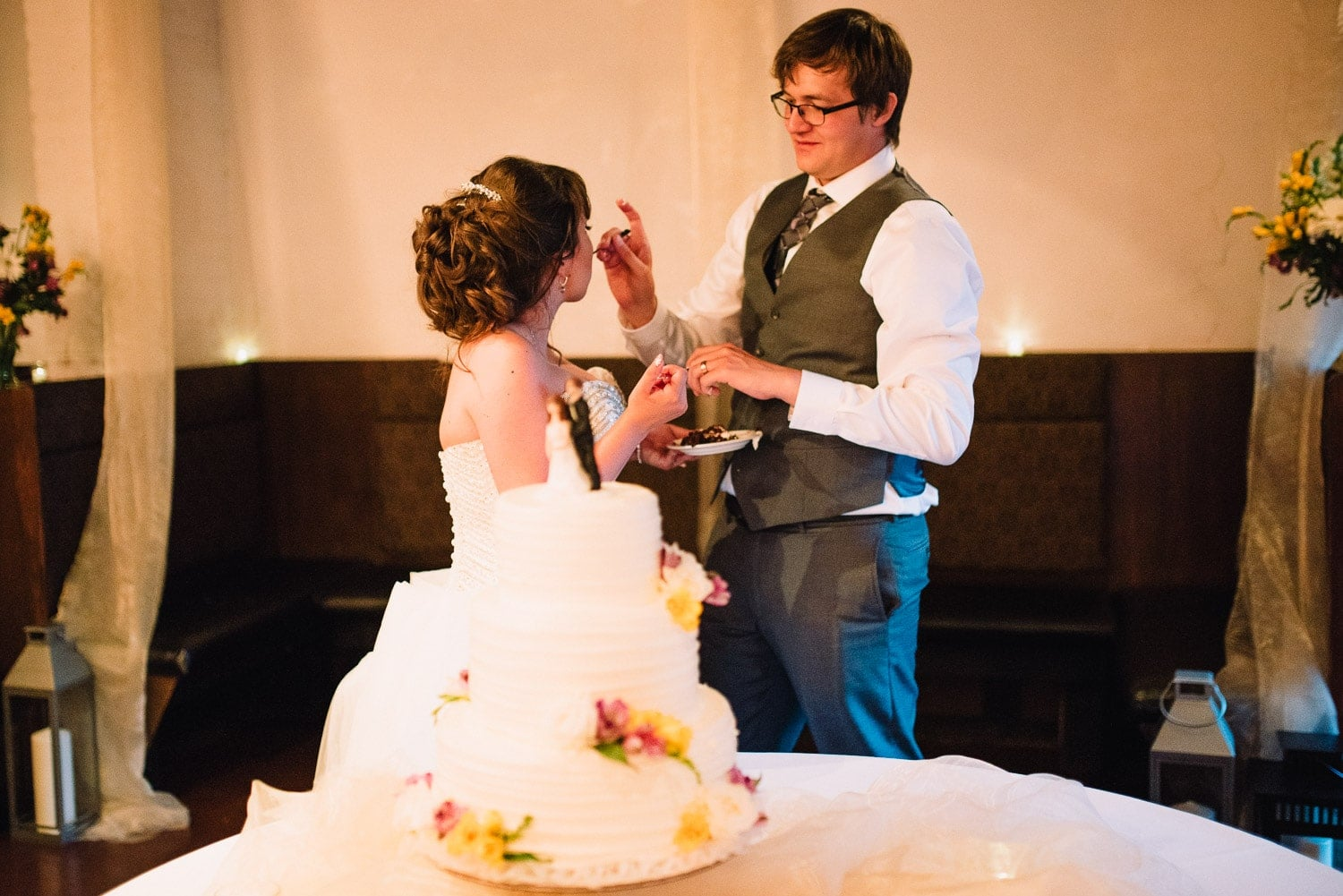 The groom is feeding wedding cake to his bride.