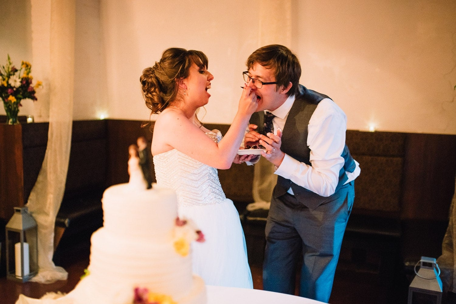 The bride is feeding wedding cake to her groom.