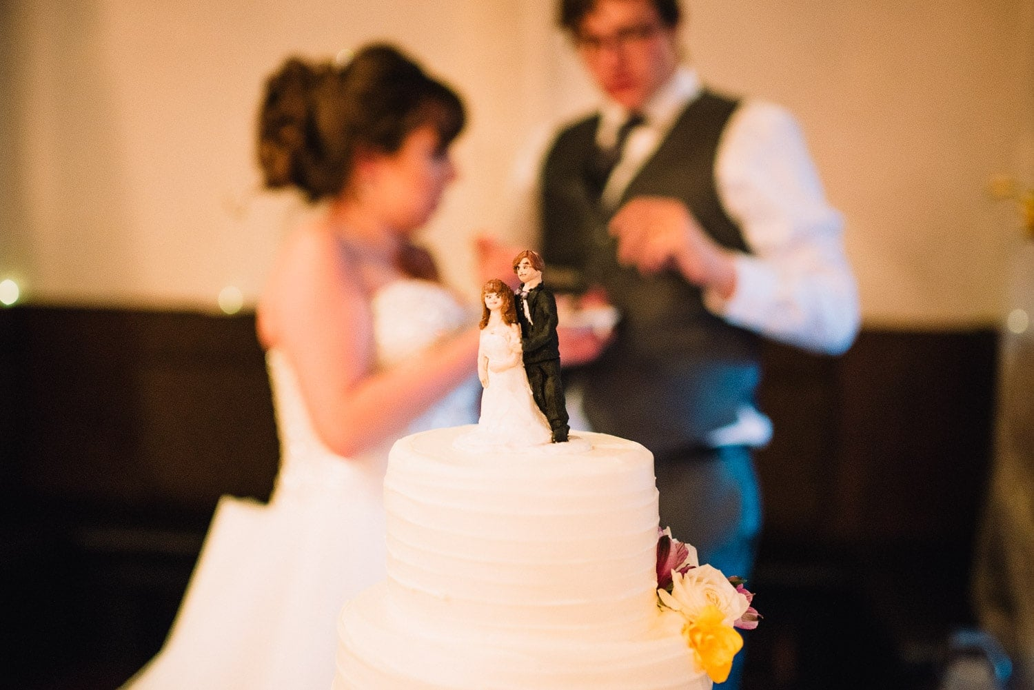 The bride and groom are blurred in the background. The wedding cake toppers are in focus in the foreground.