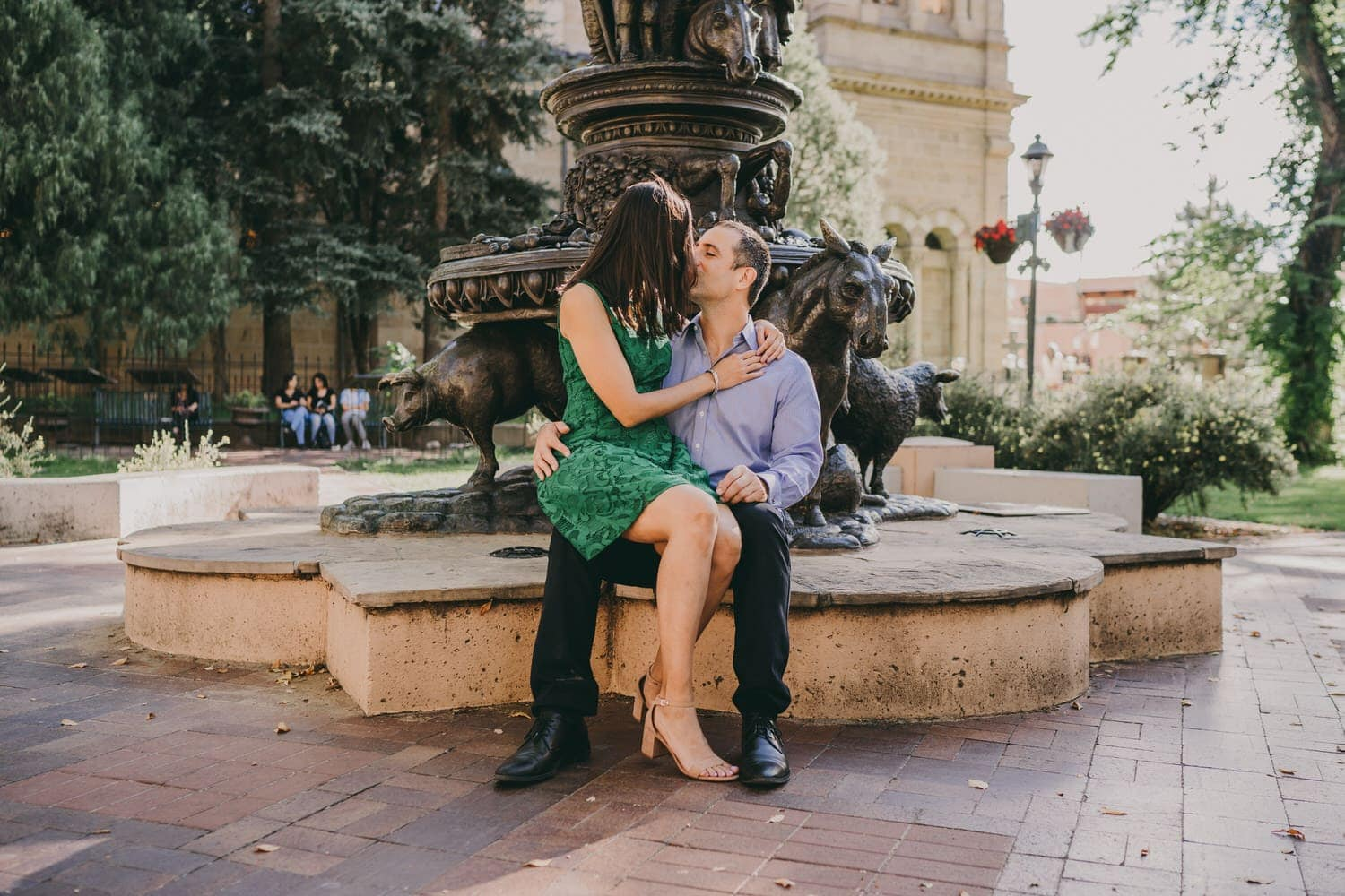 Bride and groom kissing as they sit next to a sculpture