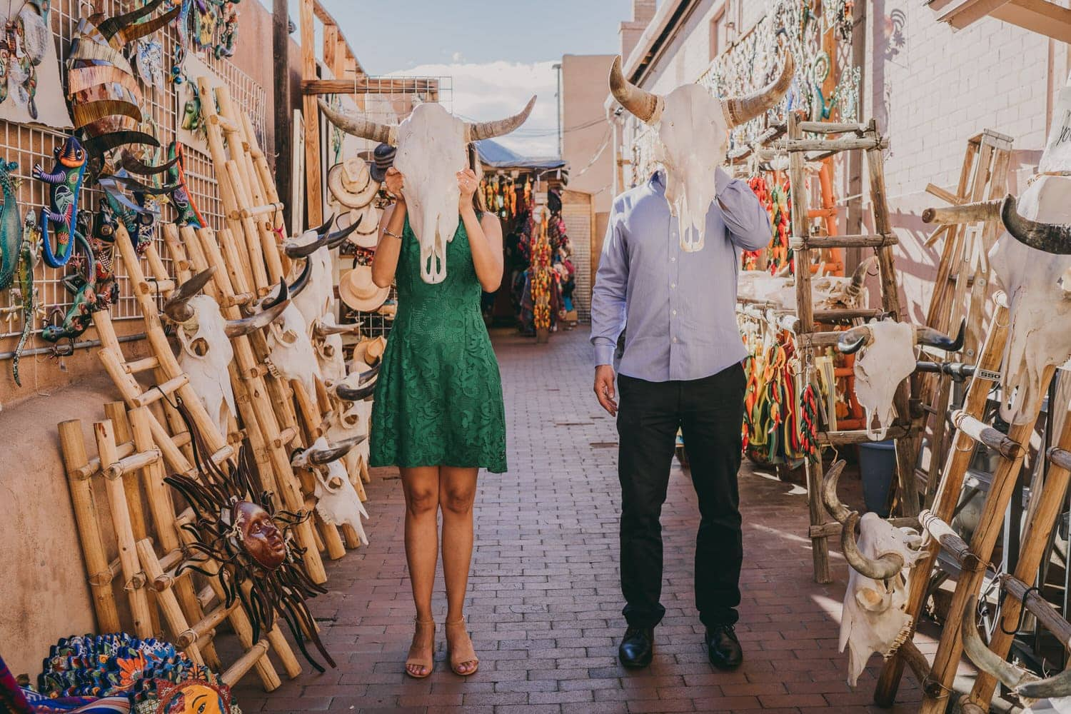 Bride and groom holding cow skulls in front of their heads in Santa Fe, New Mexico