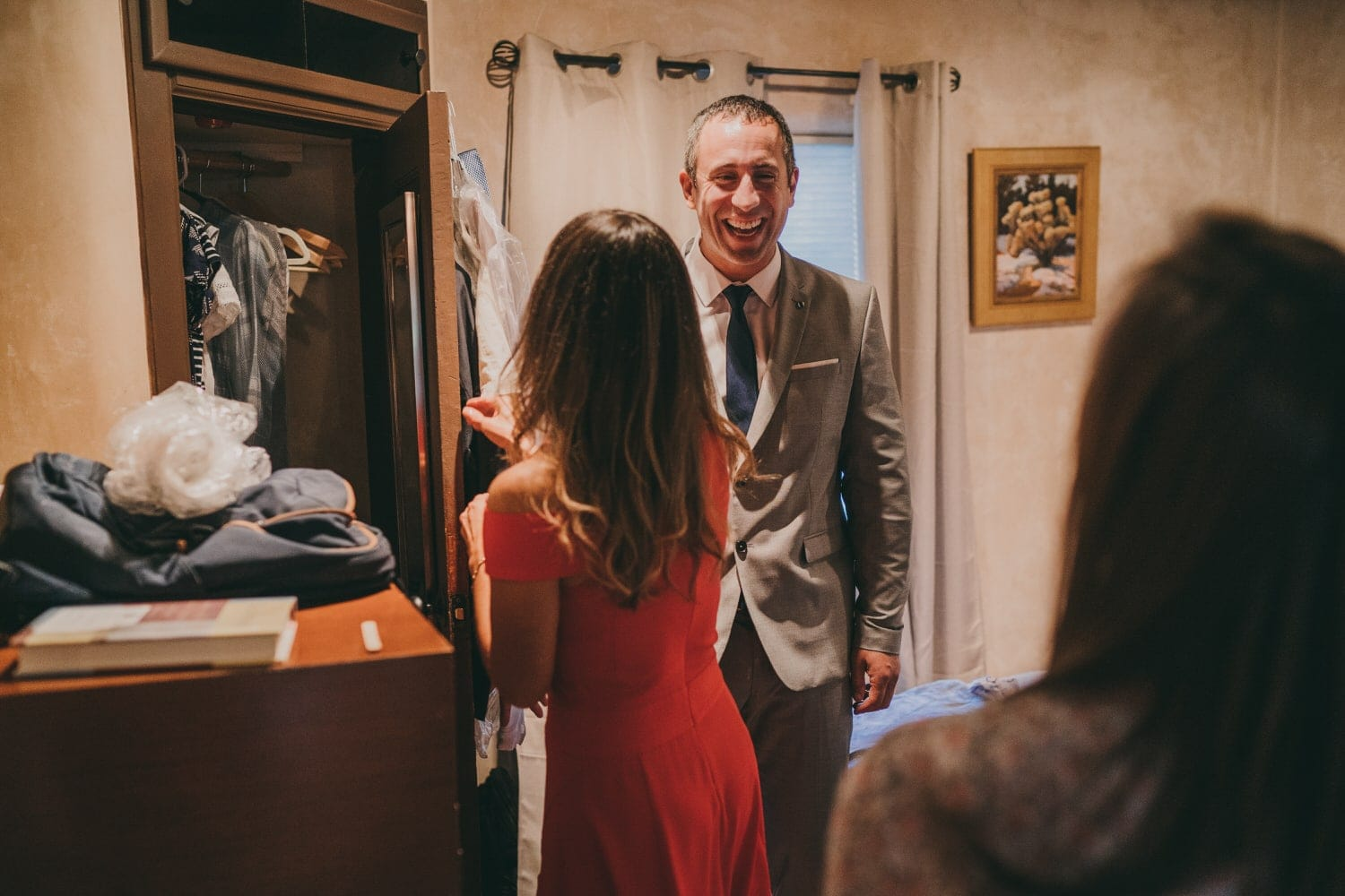Groom laughing with his sisters as they see him for the first time in his wedding suit.