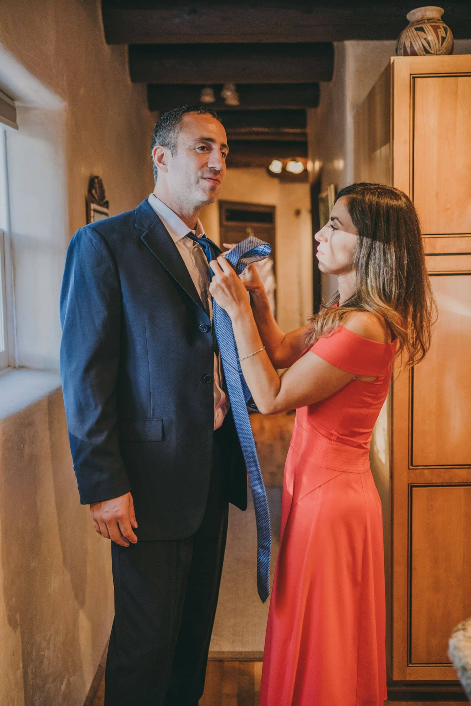 Groom's sister helping him prepare for his elopement ceremony