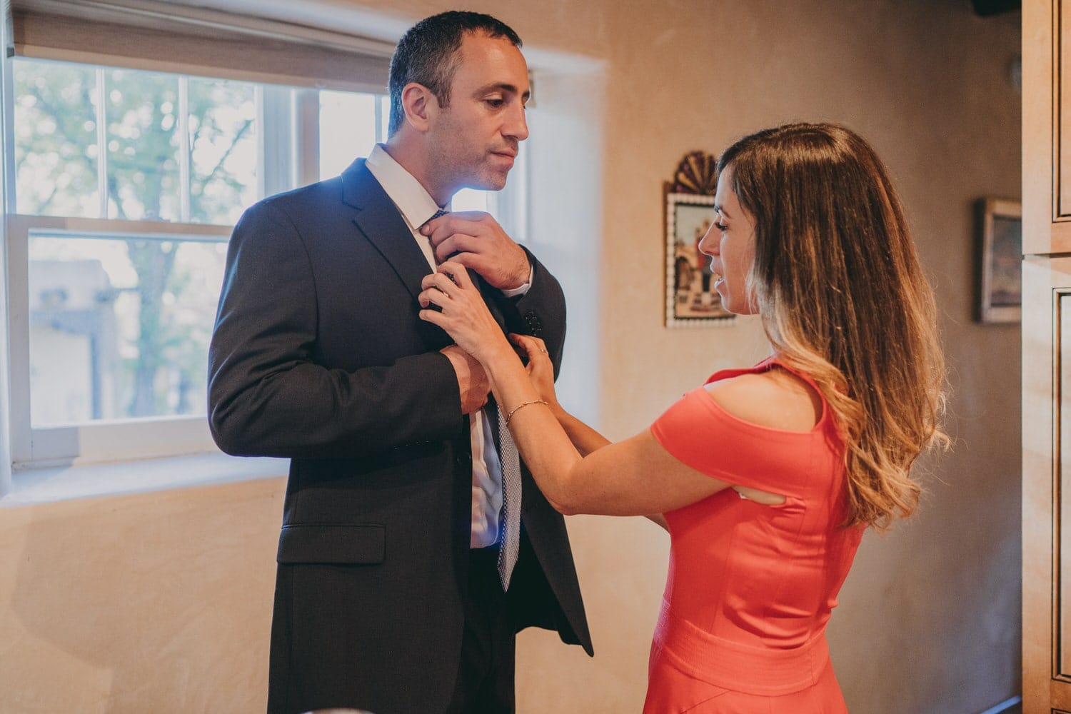 Groom's sister helping him with his tie