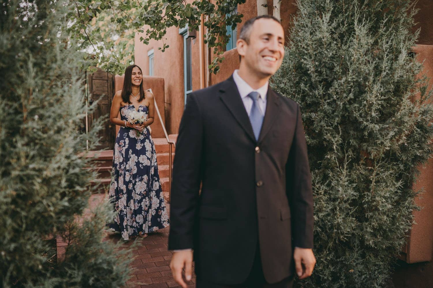 Bride laughing as she walks up behind her groom for their first look