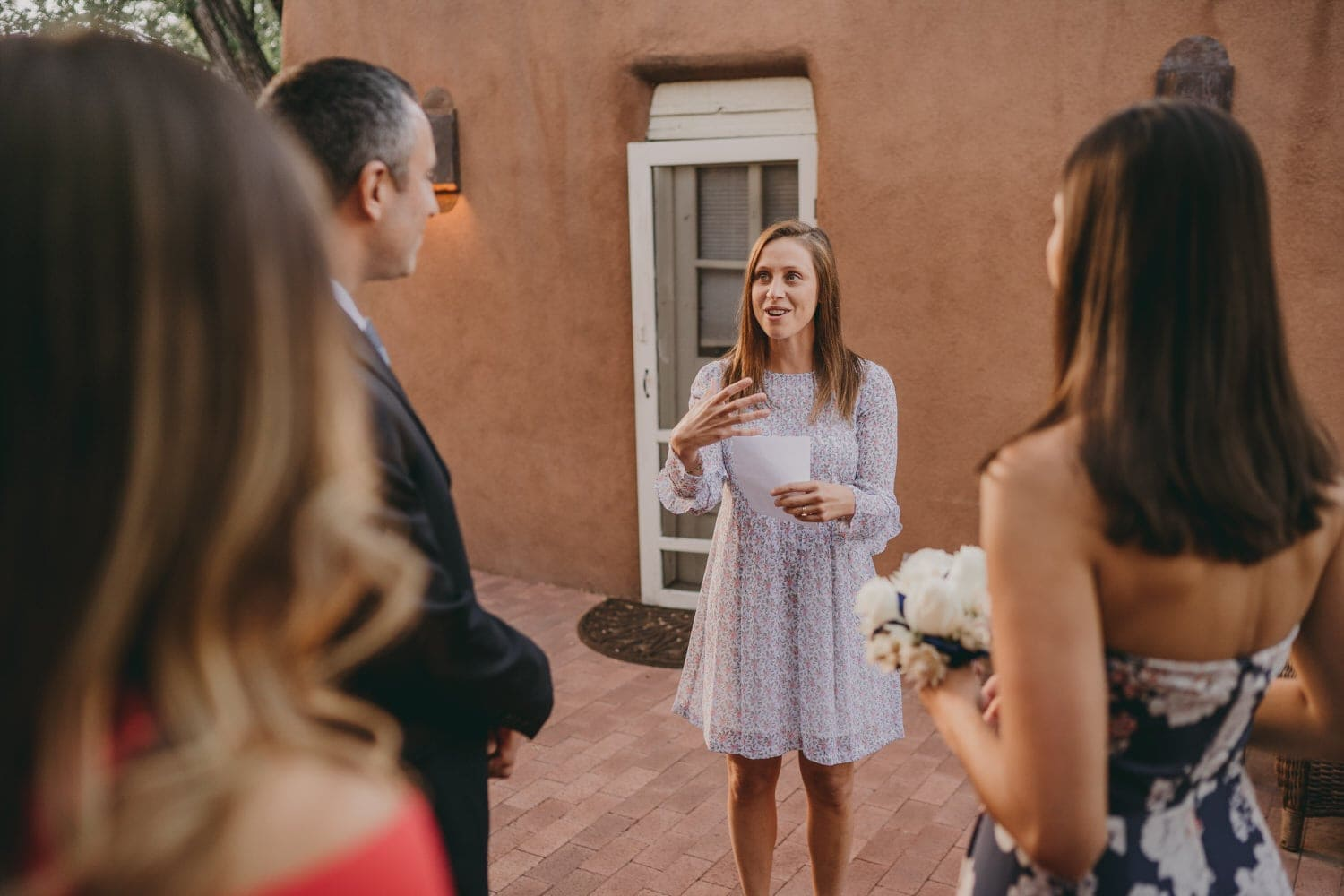 Wedding guest holding a poem and reciting it