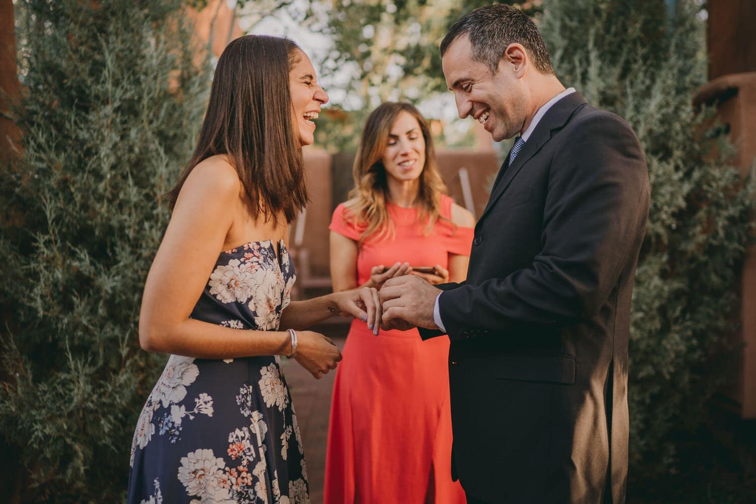 Wedding couple laughing as he slides a ring onto her finger