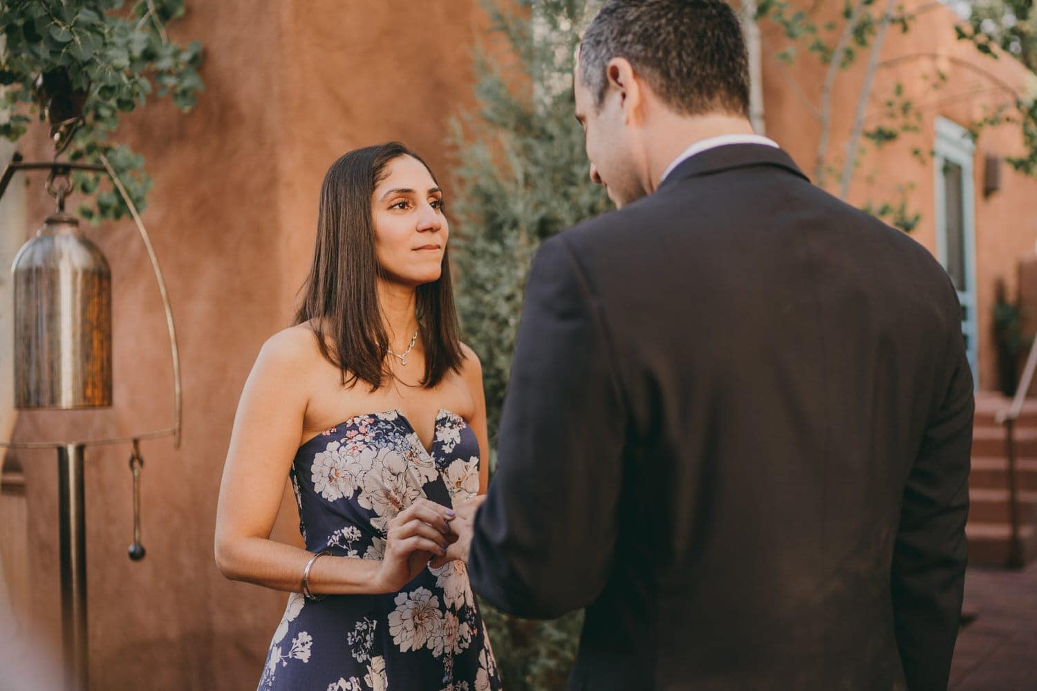 Bride starring into her groom's eyes as she places the ring on his finger