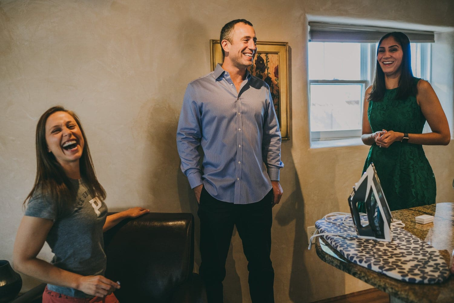 Groom laughing with his bride and sister before their elopement in Santa Fe