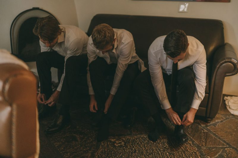 The groom and his groomsmen are tying their shoes.