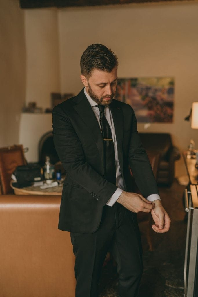 The groom is fixing his cuffs after putting his suit jacket on.