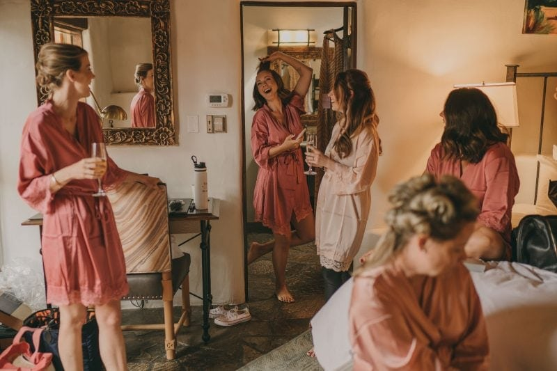 The bridesmaids are laughing and having fun as they get ready for the wedding.