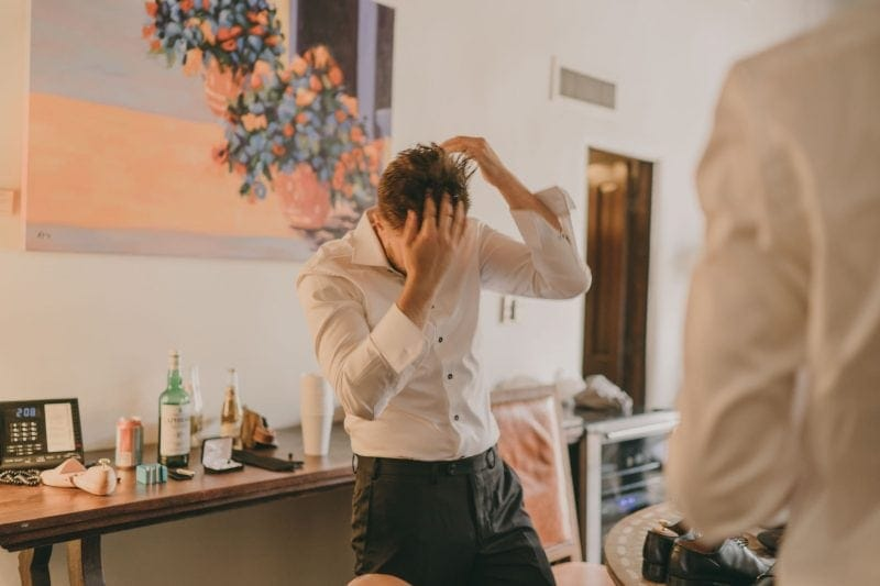 The groom is putting product in his hair.