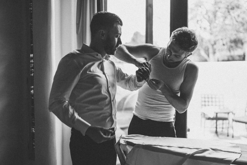 The groom's brother is helping him fix his cufflinks.