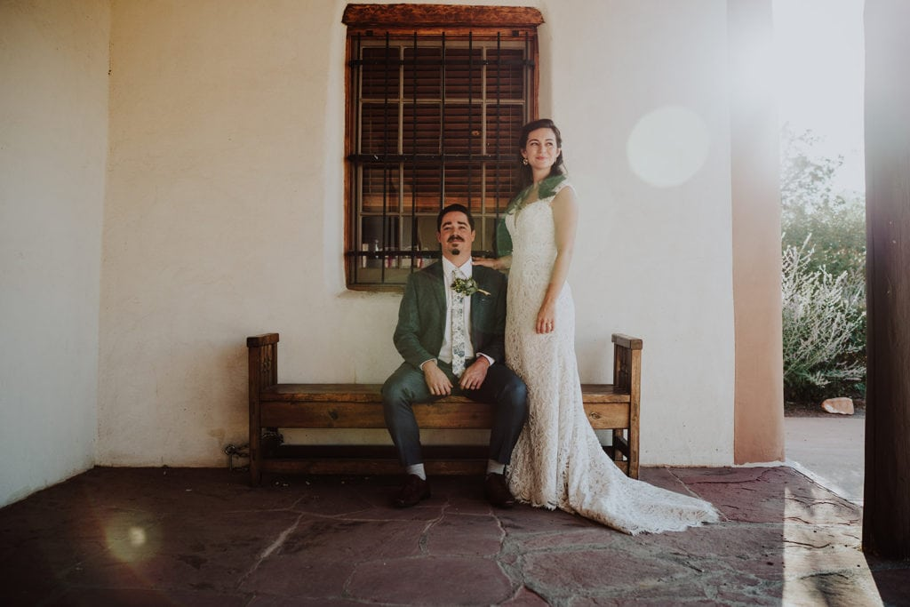 A bride and groom are posing for a picture following their destination wedding at the Museum of International Folk Art in Santa Fe.