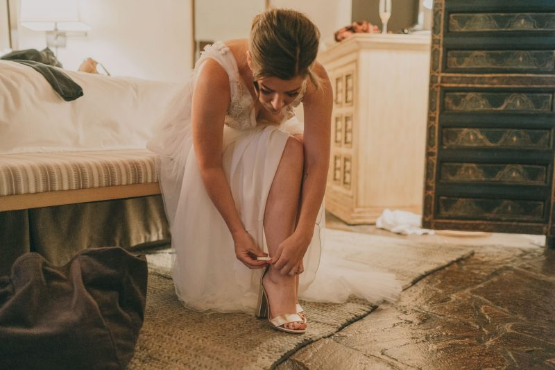 The bride is putting her shoes on.