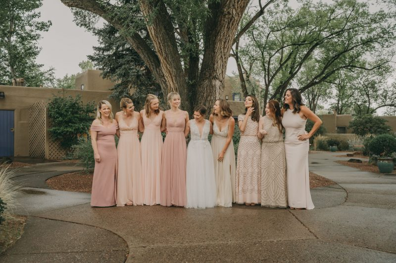 The bride is posing for a picture with her bridesmaids.