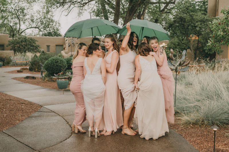 The bridesmaids are huddles under umbrellas and laughing as it starts to rain.