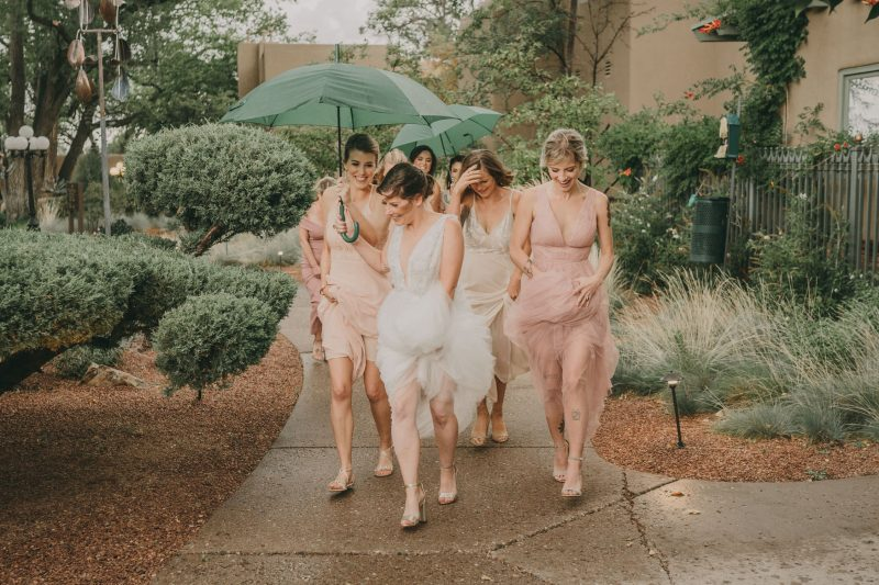 The bride and her bridesmaids are running back to their rooms, holding umbrellas above their heads as it starts to rain.