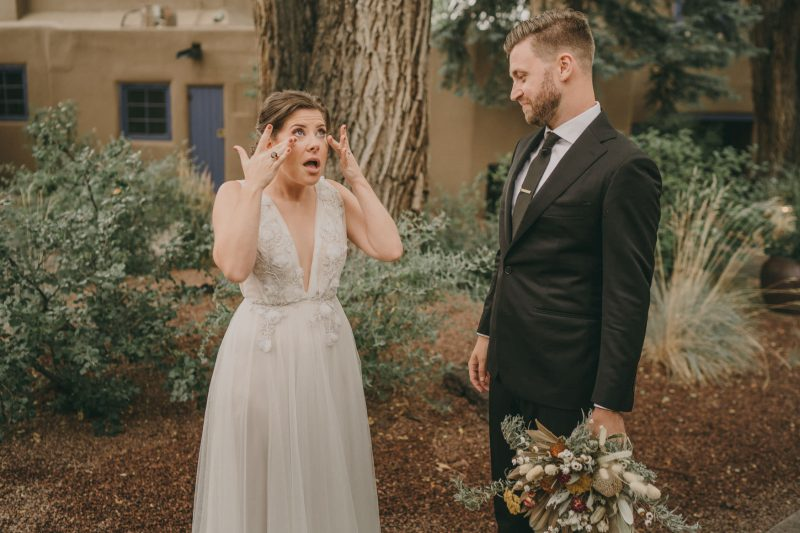 The bride is wiping tears from her eyes.