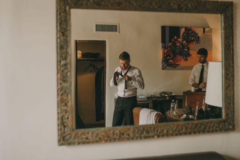 The groom can be seen in the reflection of a mirror tying his tie.