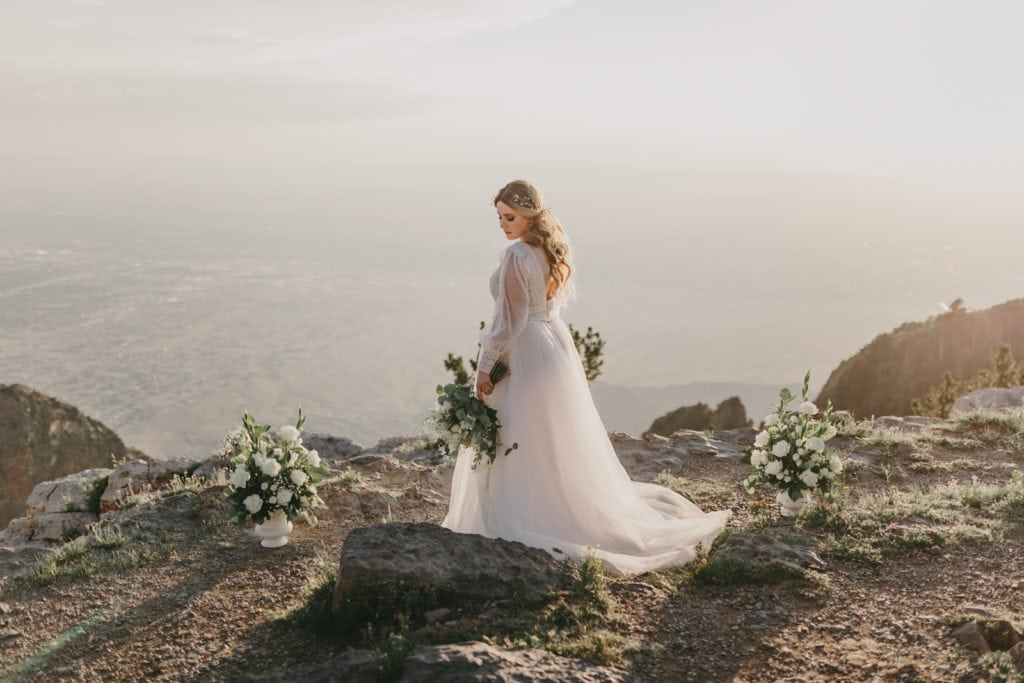 The bride is holding her bouquet near the edge of Sandia Crest.