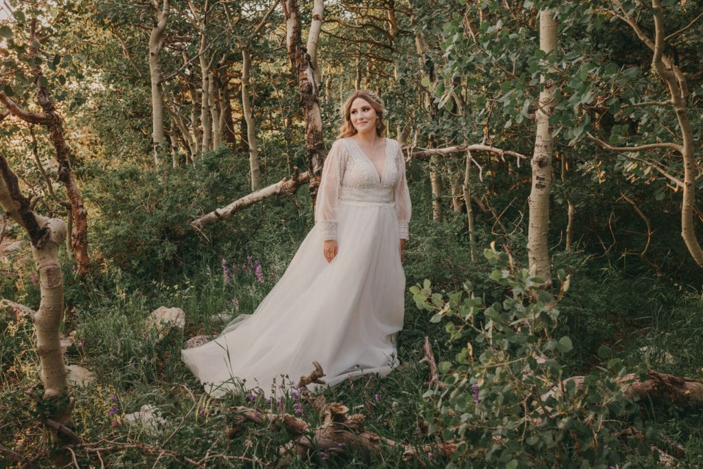 The bride is smiling surrounded by trees at the top of the Sandia Mountains.