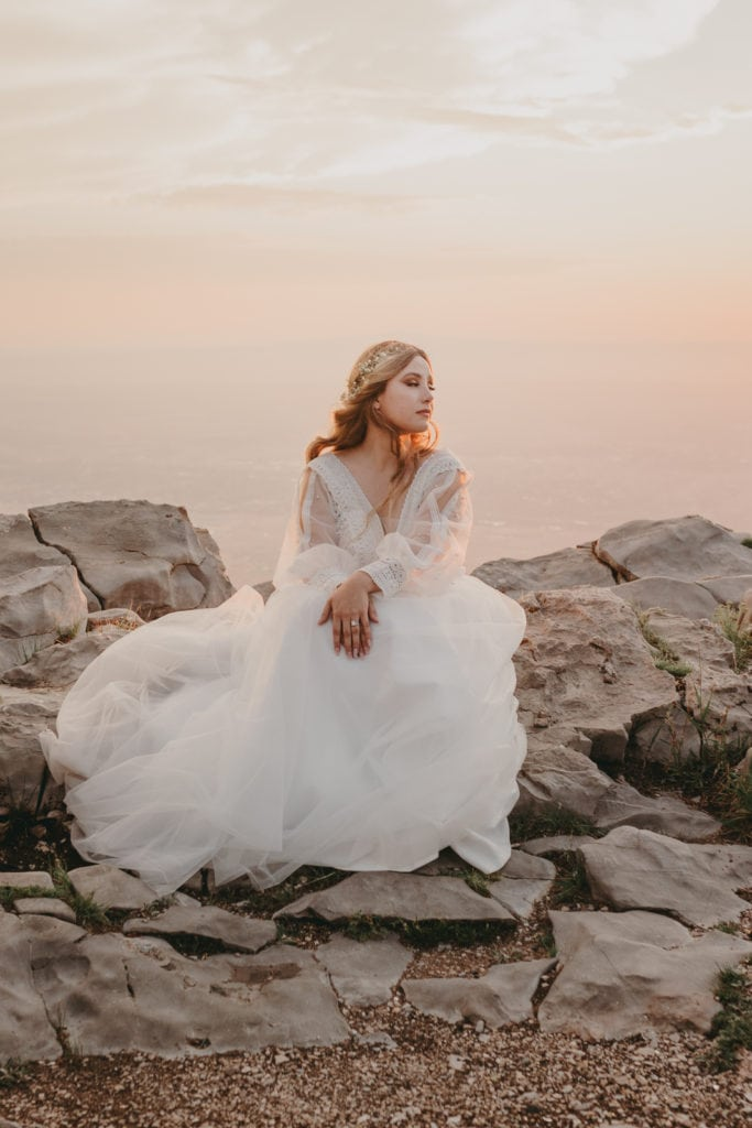 The bride is sitting on stones near the edge of Sandia Crest