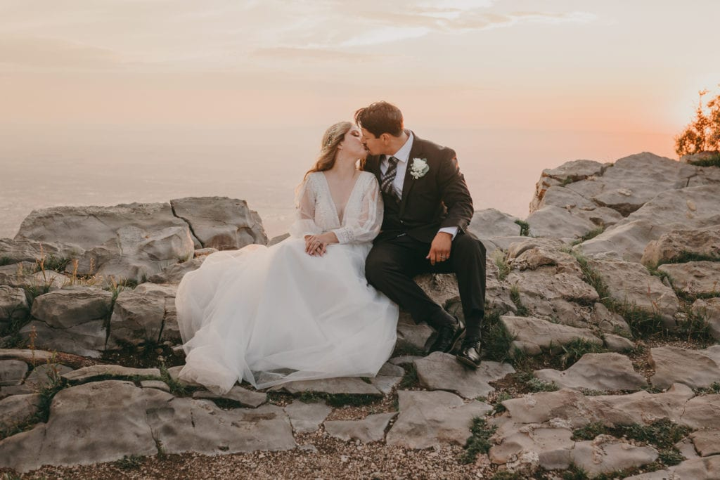 The bride and groom are kissing while sitting on stones at the top of the Sandia Mountains