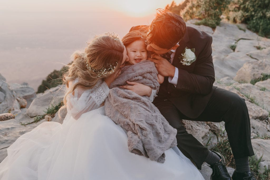 The bride and groom are kissing their young son as the sun sets, atop Sandia Crest