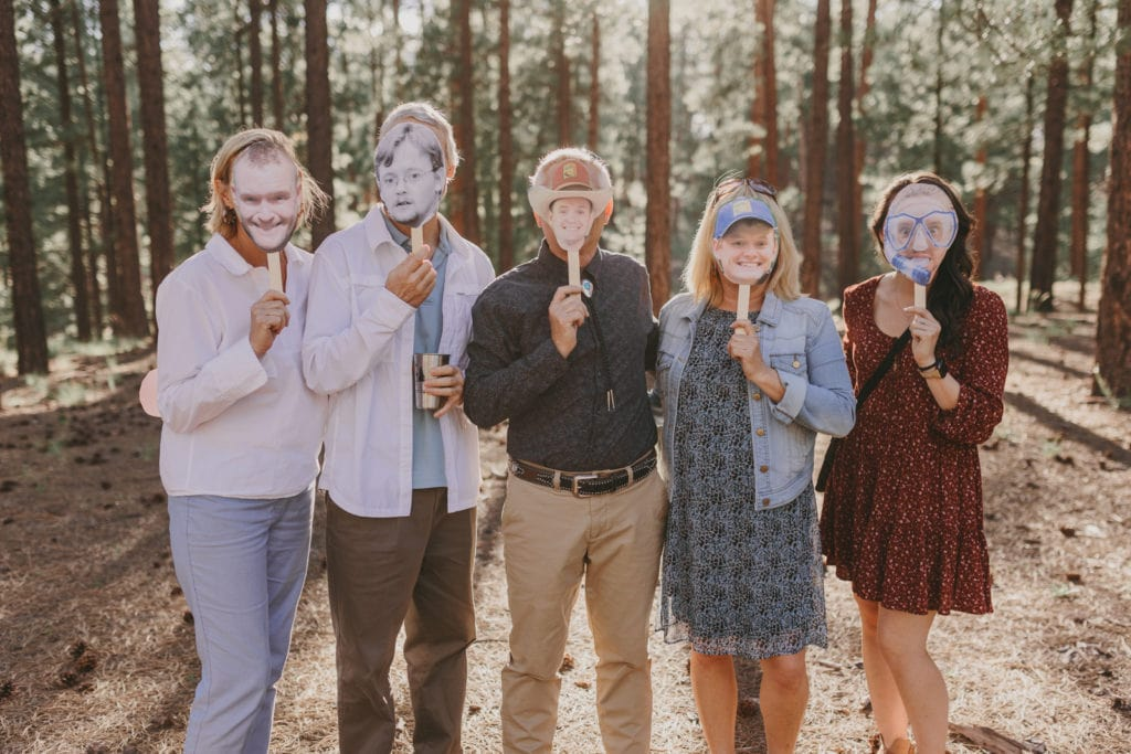 The wedding guests are holding up cut out photos of the groom in front of their faces.