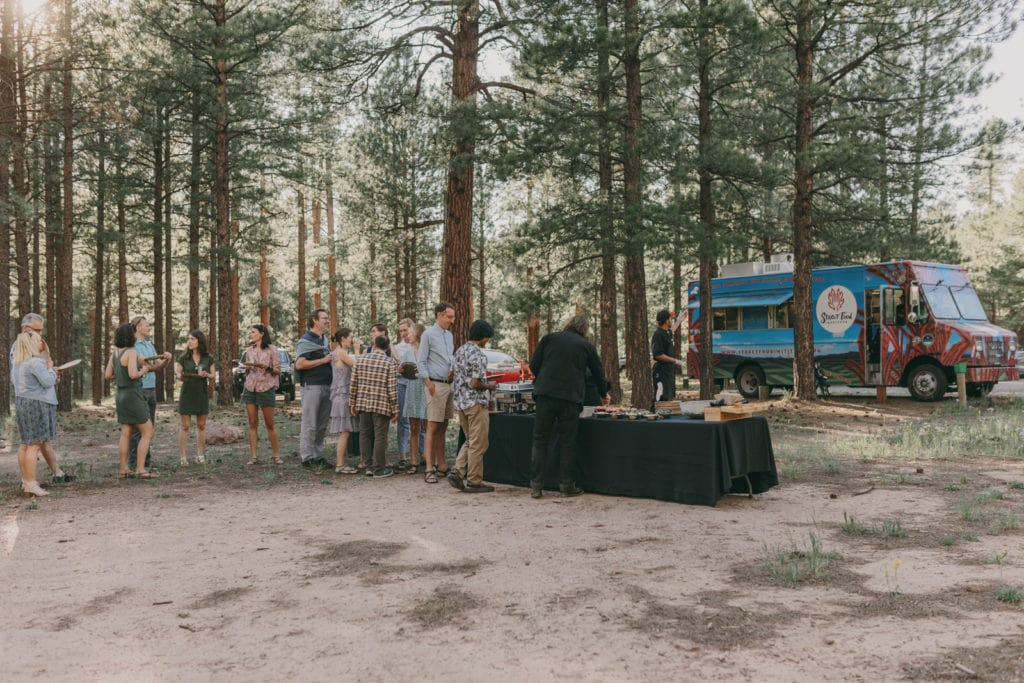 The wedding guests are waiting in line at the Santa Fe Food Institute food truck.