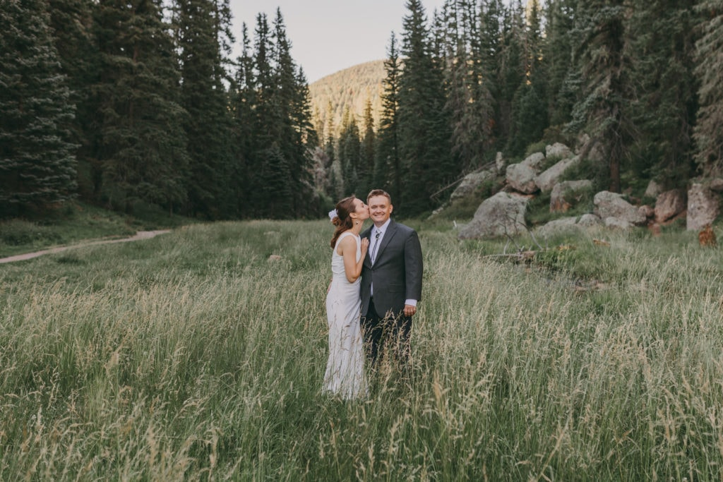 The bride and groom are standing in mountain grass following their destination wedding in Jemez, New Mexico.