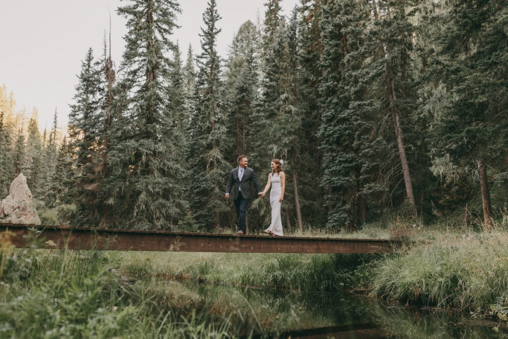 The bride and groom are holding hands as they cross the bridge over the river in Jemez, New Mexico.